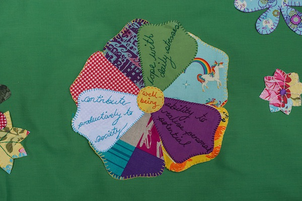 the 3 elements of wellbeing hand-embroidered onto a fabric flower