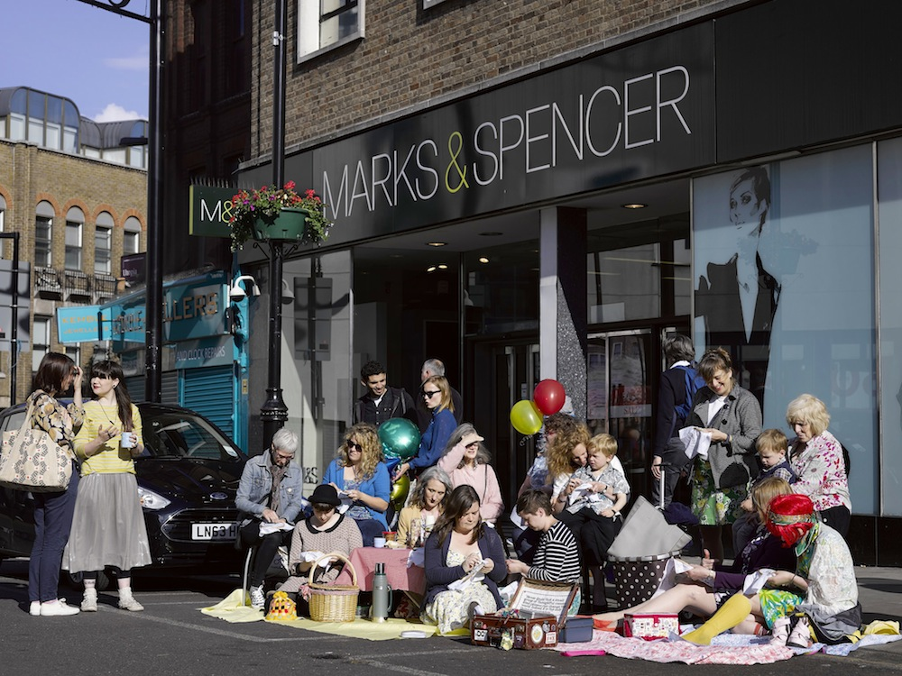 members of the Craftivist Collective from across the London & the South East setting up their pretty picnic stitch-in to intrigue passersby, create a safe space for conversation with the public & M&S staff