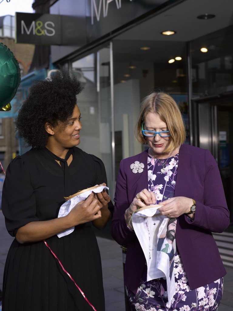 Craftivist's Kandice (left) & Caroline stitching outside M&S in Islington London. Caroline is making a bespoke hanky for M&S Board member Mr Vindi Banga who is Sikh so she her practicing Sikh friend recommended a particular message to stitch on linked to social justice for Sikhs